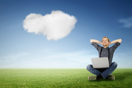 a man with laptop is relaxing on a green meadow with a cloud in the sky in the background Stock Photo