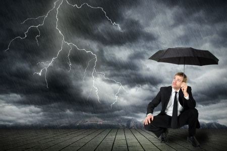 to crouch: a man in a suit and umbrella seeks shelter from flashes and rain
