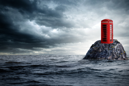 telephone box: a red telephone box stands lonely in the ocean on a rock