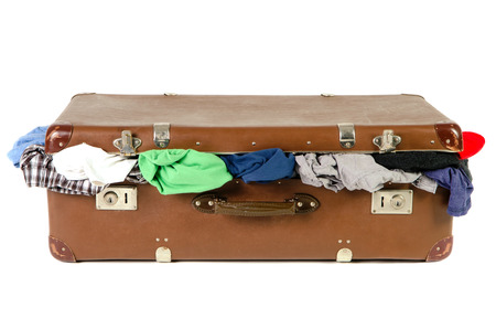 overflow: old brown suitcase full with clothes isolated before white background