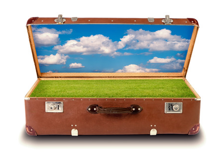 a natural landscape in an open suitcase isolated before white background