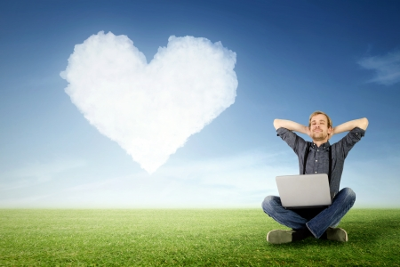 take it easy: a man sits relaxed with laptop on the meadow with a cloud in heart shape in the background Stock Photo