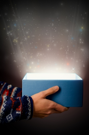 openly: two hands hold a blue box with beam of light before black background