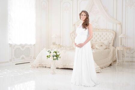 happy pregnant woman in a light interior Stock Photo