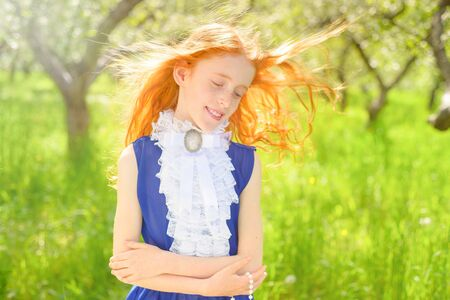 redhair girl in a sunny garden Stock Photo