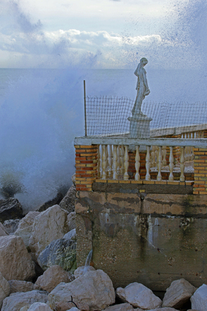 Rough sea in winter in Porto Recanati in the province of Ancona Italy near Monte Conero with the sea crashing against rocks and a statue on the terrace of a boarded up restaurant
