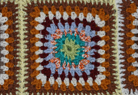 brightly coloured crocheted panel in a homemade woollen blanket with a mosaic design