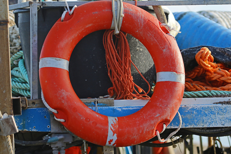 life buoy or life saving ring hanging up on a fishing boat on the Adriatic sea in the port or harbour of Numana near Ancona in Italy