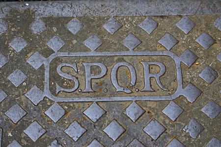 Latin SPQR en una alcantarilla o tapa de desagüe en las calles de Roma, Italia, representando el latín SenatusQue Populus Romanus Foto de archivo