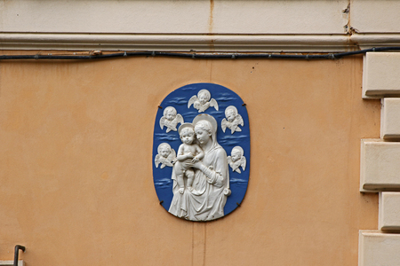 detail of an ancient plaque on a wall in the streets of Rome, Italy showing the Virgin Mary or Madonna and child with angels surrounding them