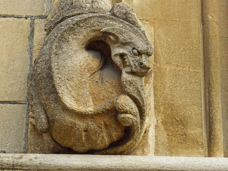A weather worn or weather-beaten stone gargoyle or grotesque on the wall of a college in Oxford part of the university in sandstone or limestone from the Cotswold region of Oxfordshire in England