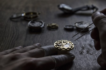 hands in pocket: Watch maker is repairing a vintage vechanical watch Stock Photo