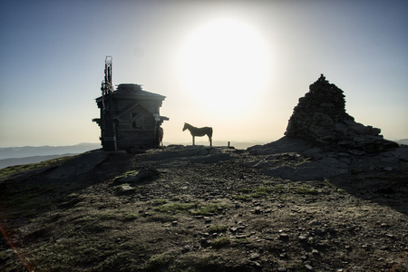Silhouette of horse, building, mountian, sun, sky