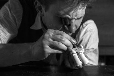 Zegarmistrz naprawia mechaniczne zegarki w swoim warsztacie