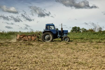 Tractor is working in the field, day