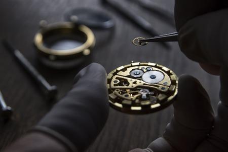 Zegarmistrz naprawia zegarki mechaniczne w swoim warsztacie Zdjęcie Seryjne