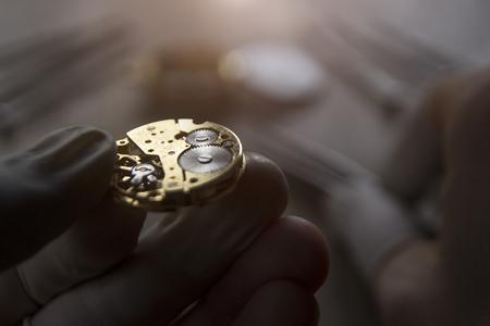 時計は彼のワーク ショップで機械式時計を修理します。