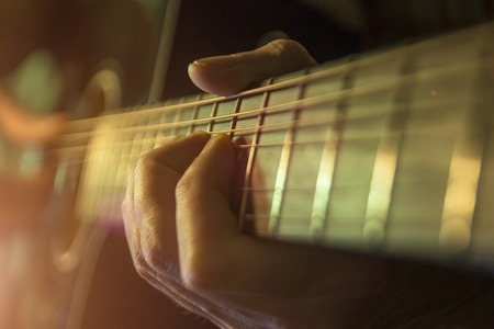 Man with guitar, male hand playing on acoustic guitar. Close-up. Stock Photo