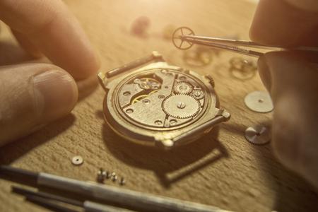 時計職人は彼のワークショップで機械式時計を修理しています 写真素材