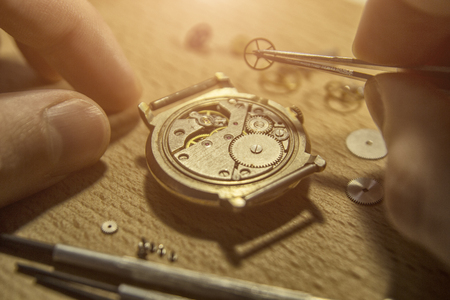 Watchmaker is repairing the mechanical watches in his workshop Banco de Imagens