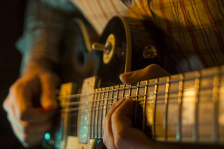 Play the electic guitar, close up