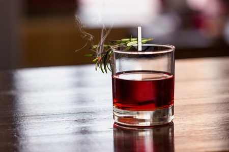 Nice red cocktail with a branch of rosemary