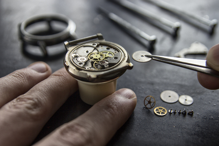 Watchmaker is repairing the mechanical watches in his workshop 版權商用圖片 - 97795834