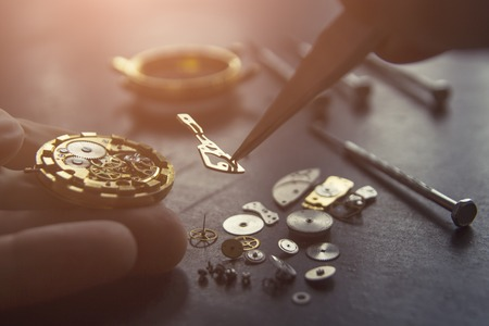 Watchmaker is repairing the mechanical watches in his workshop Фото со стока