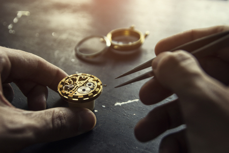 Watch maker is repairing a vintage automatic watch. Фото со стока