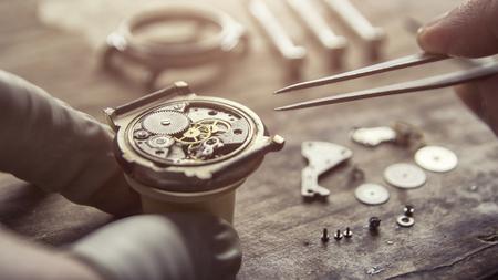 Der Uhrmacher repariert die mechanischen Uhren in seiner Werkstatt