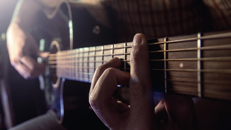 male hand playing on acoustic guitar. Close-up.