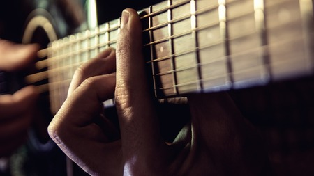 Man with guitar, male hand playing on acoustic guitar. Close-up. Фото со стока