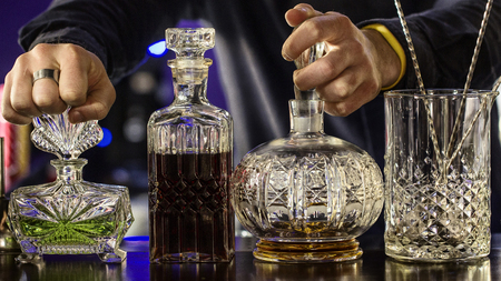 The bartender is holding the bottles, close up