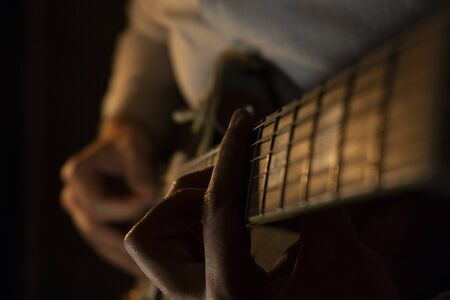 mans hands play the guitar