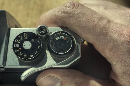 Setting the shutter speed on an analog camera, mans hand