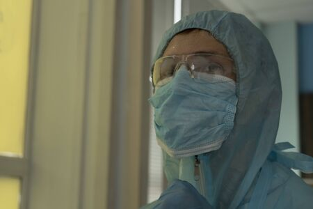 Tired doctor in protective suit at the hospital
