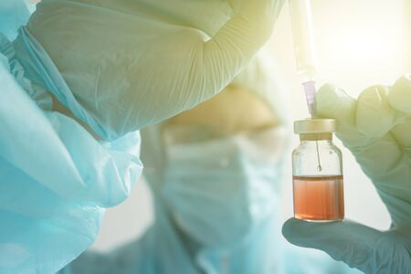 Development of a vaccine, the doctor holds an ampoule in his hand