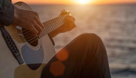 Guy plays guitar at sunset
