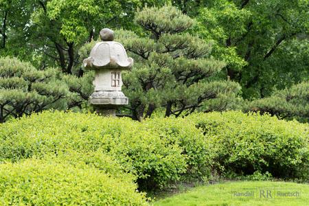 Stone lantern, trees, and shrubs in a Japanese garden Stock Photo
