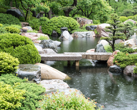 A stone bridge crosses a pond in a Japanaese garden