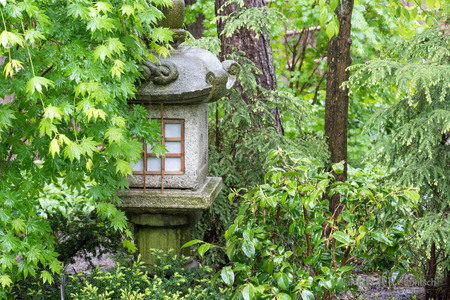 A stone lantern is obscured by shrubs in a Japanese garden Stock Photo