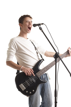 The young guy with a bass guitar sings in a microphone on a white background.