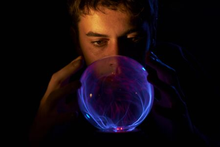 The man looks at patterns in a glass sphere.