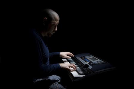 De man speelt een elektrische piano. Stockfoto