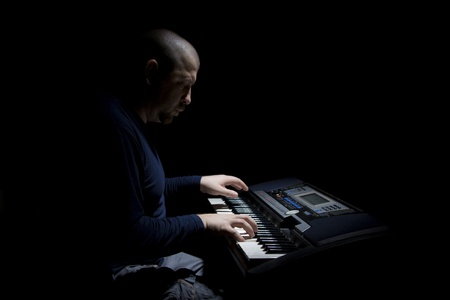 The man plays electric piano.