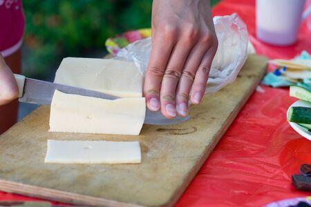 Cutting cheese on cutting board
