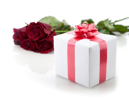 A bouquet of roses and gift box with red ribbon on white background. Stock Photo