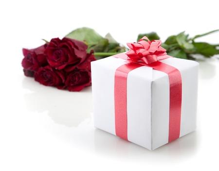 Een boeket van rozen en gift box met rood lint op witte achtergrond.