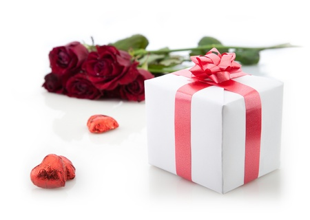 A bouquet of roses and gift box with red ribbon on white background. Stock Photo - 12391388