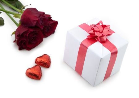A bouquet of roses and gift box with red ribbon on white background. photo